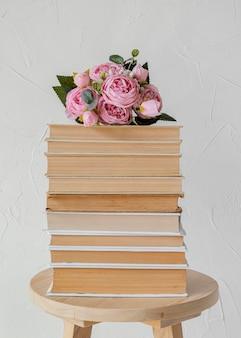 Arreglo con pila de libros y rosas.