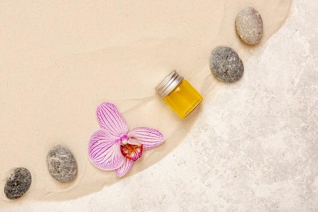 Arreglo plano con aceite, piedras y flores.