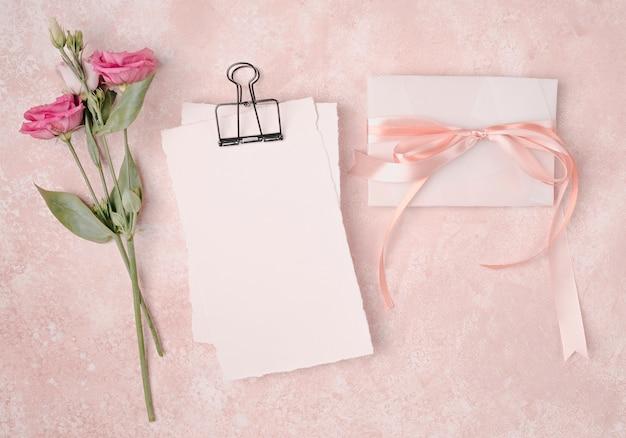 Arreglo plano de boda con invitación y flores.
