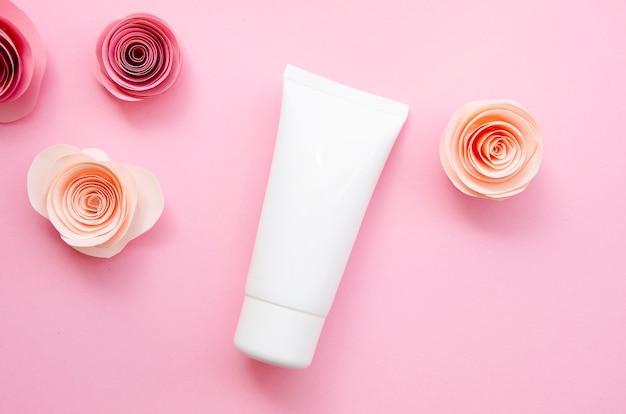 Arreglo plano con botella de crema y rosas