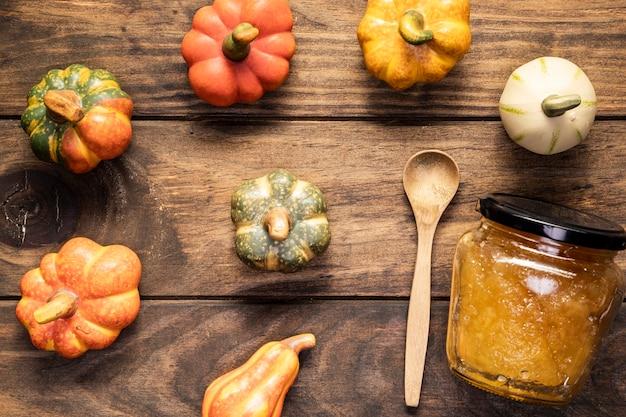 Arreglo plano de calabazas con tarro de mermelada y cuchara.