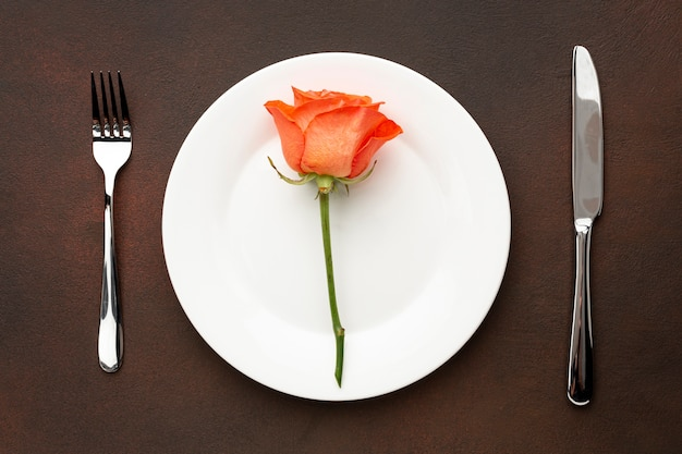 Arreglo plano para la cena de san valentín con rosa naranja