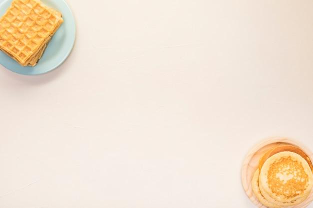 Arreglo plano de comida con panqueques y waffles.