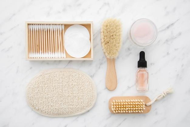 Arreglo plano con cosméticos sobre mesa de mármol.