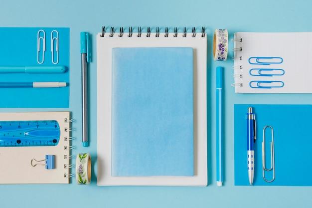 Arreglo plano de cuadernos y bolígrafos