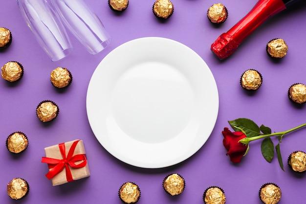 Arreglo plano laico con chocolate y plato blanco.