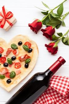 Arreglo plano con pizza y botella de vino.