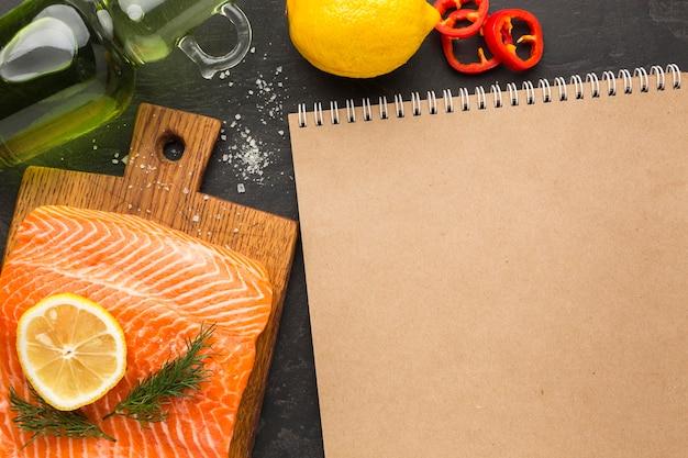 Arreglo plano de salmón y cuaderno