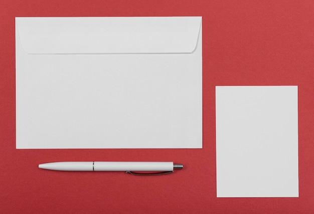 Arreglo plano de sobre y bolígrafo