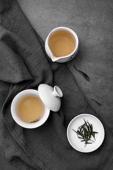 Arreglo plano con tazas de té y hierbas.