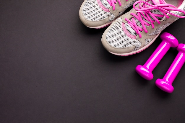 Arreglo plano con zapatos rosas y pesas
