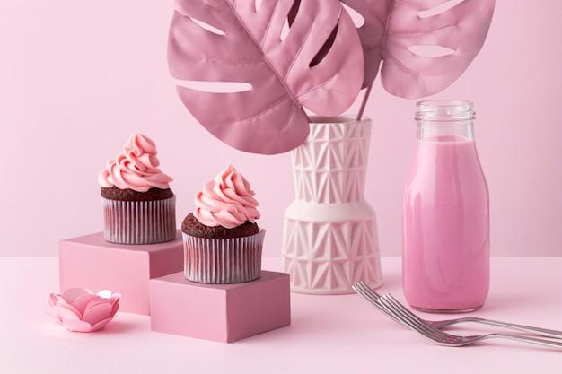 Arreglo de plantas monstera y cupcakes rosas