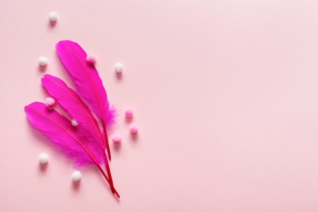 Arreglo de plumas rosas y bolas de algodón.