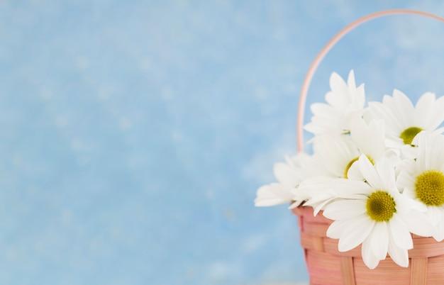 Arreglo de primer plano con canasta de flores y espacio de copia