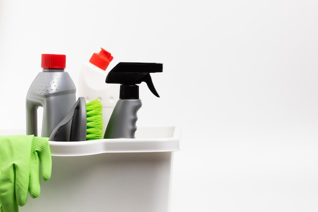 Arreglo con productos de limpieza y guantes en lavabo.