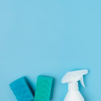 Arreglo con productos de limpieza sobre fondo azul.