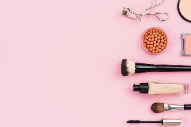Arreglo de productos de maquillaje sobre fondo rosa.