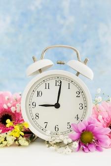 Arreglo con reloj y flores de colores.