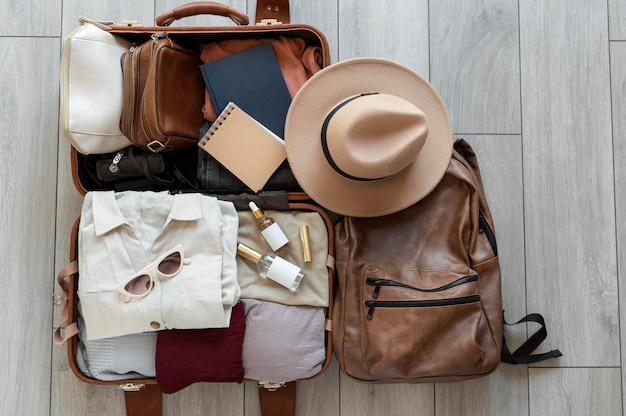 Arreglo de ropa y accesorios en una maleta.