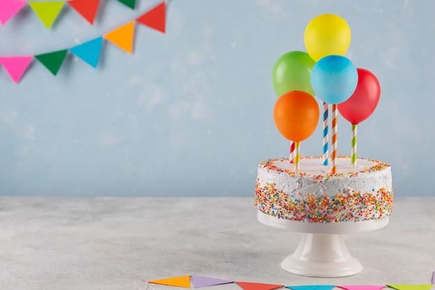 Arreglo con sabroso pastel y globos.