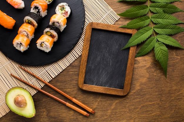 Arreglo de sushi plano con pizarra negra.