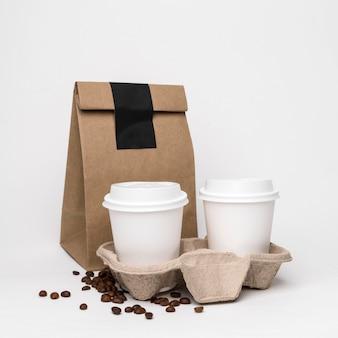 Arreglo con tazas de café y bolsa de papel.
