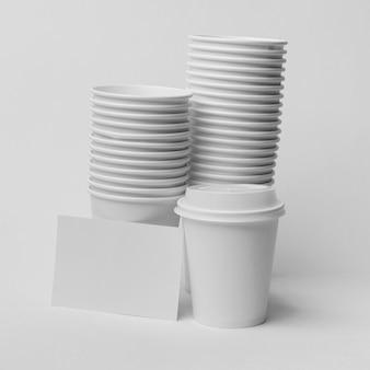 Arreglo con tazas de café y trozo de papel.
