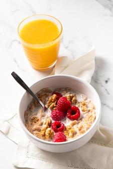 Arreglo de tazón de cereales saludables con jugo de naranja