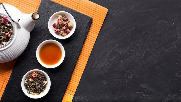 Arreglo de té de hierbas y su ingrediente en piedra pizarra.