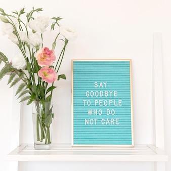 Arreglo con texto y flores.