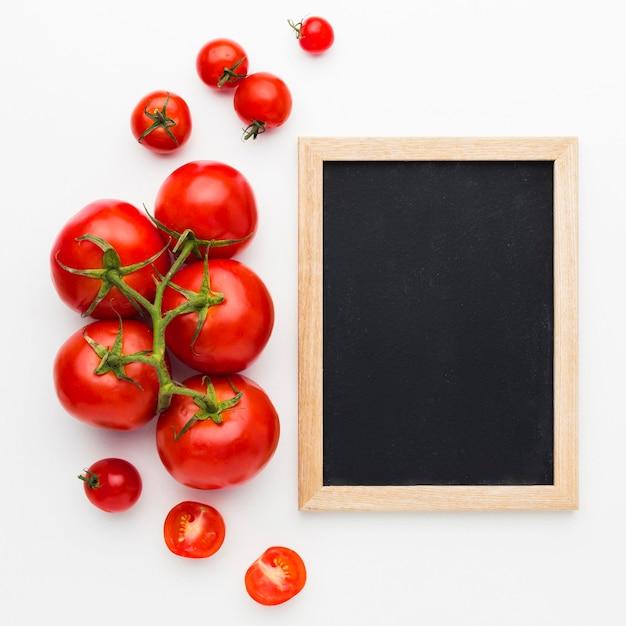 Arreglo de tomates con pizarra vacía