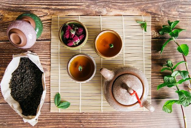 Arreglo tradicional de la ceremonia asiática del té con pétalos de rosa y ramita de menta en el escritorio de madera