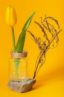 Arreglo con un tulipán en un jarrón.
