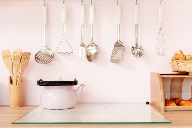 Arreglo con utensilios de cocina y tetera.