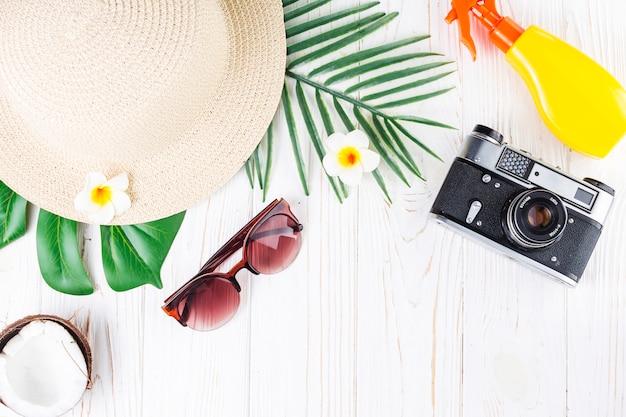 Arreglo de vacaciones tropicales con protector solar, cámara, cabaña, lentes de sol, coco, flores y hojas de palma.