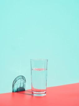 Arreglo con vaso de agua cerca de la pared azul