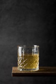 Arreglo con vaso de bebida en mesa de madera