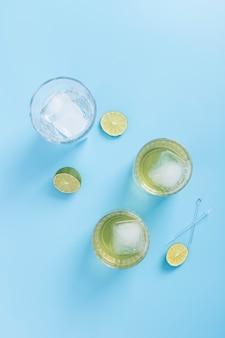 Arreglo con vasos de limonada y cubitos de hielo.