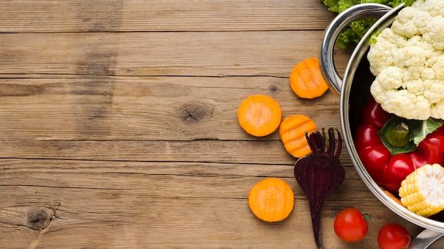 Arreglo de verduras coloridas sobre fondo de madera con espacio de copia