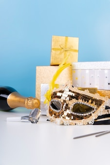 Arreglo de vista frontal con máscara de lentejuelas y champán