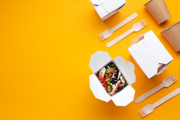 Arreglo de vista superior con cajas de ensalada y vajilla