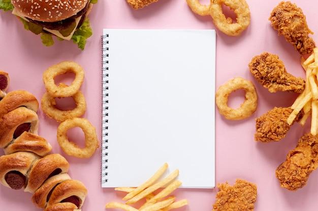 Arreglo de vista superior con comida y cuaderno