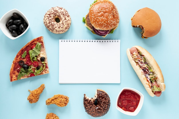 Arreglo de vista superior con comida rápida y cuaderno