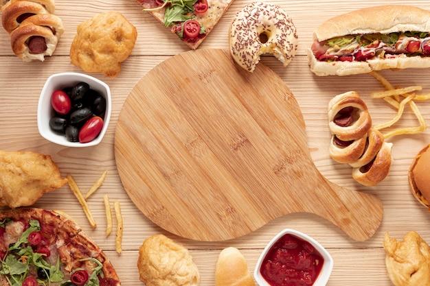 Arreglo de vista superior con comida y tabla de cortar