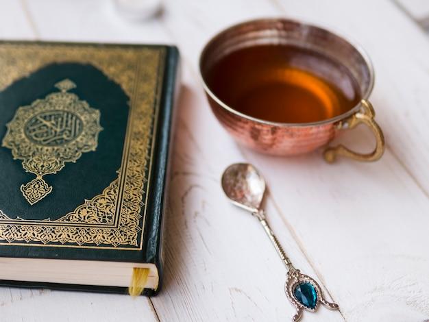 Arreglo de vista superior con corán, té y cuchara.
