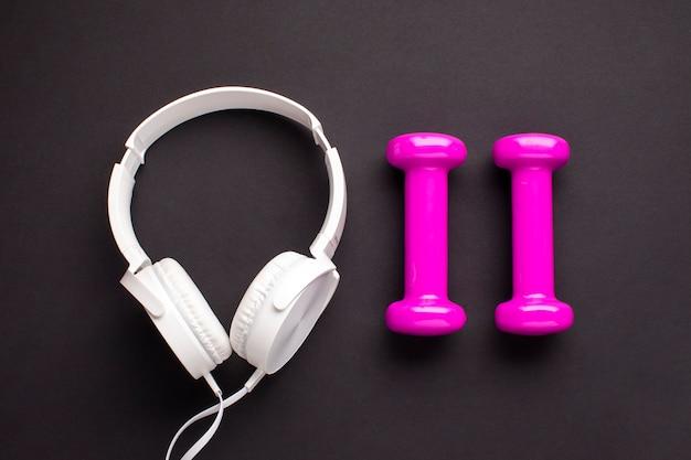 Arreglo de vista superior con pesas rosa y auriculares