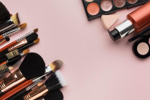 Arreglo de vista superior con pinceles de maquillaje y productos