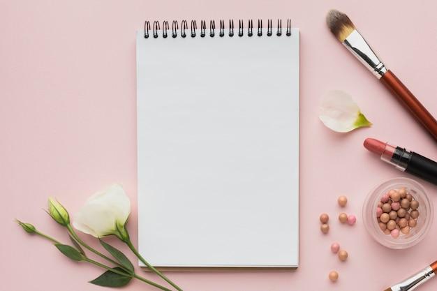 Arreglo de vista superior con productos de maquillaje y cuaderno