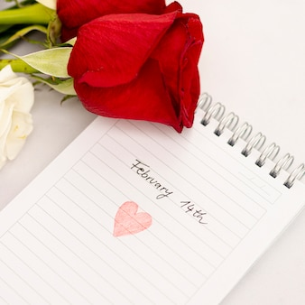 Arreglo de vista superior con rosas en el cuaderno