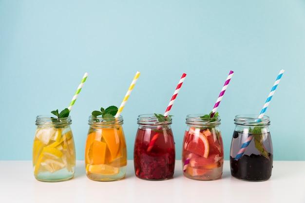 Arreglo de zumo de fruta fresca con pajitas.